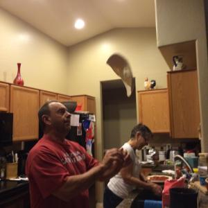 Dave shows he's got skillz by tossing the pizza in the air as he readys it for the pan.
