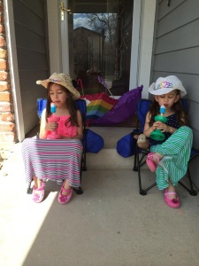 Kaiya and Mylee enjoy a popsicle on their front porch.